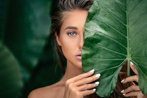 Retrato de lujo de una hermosa joven con maquillaje natural tiene una gran hoja verde en verde borrosa