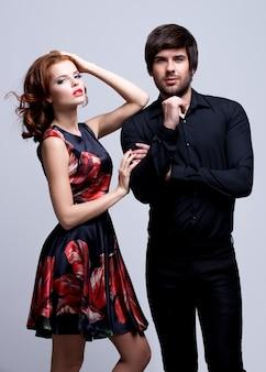 Retrato de lujo joven pareja enamorada posando en estudio vestida con ropa clásica.