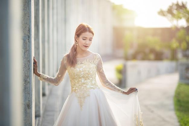 Retrato con luz natural de una novia asiática en traje de novia