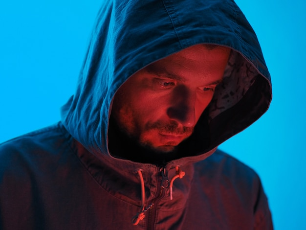 Retrato de luz de neón de hombre serio con capucha. brillante luz azul roja.