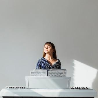 Retrato de una luz del sol de la mujer joven que cierra sus ojos que disfrutan de la luz del sol que se sienta delante de piano