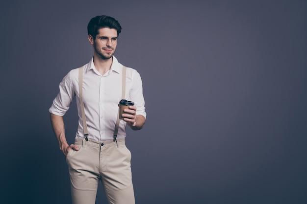 Retrato de macho líder exitoso hombre de negocios bebiendo café para llevar caliente pausa vestida ropa formal camisa beige tirantes pantalones especificaciones.