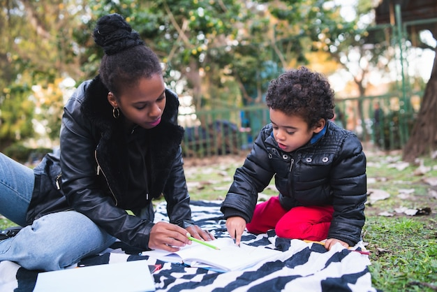 Retrato de una madre afroamericana con su hijo jugando y divirtiéndose juntos al aire libre en el parque. familia monoparental.