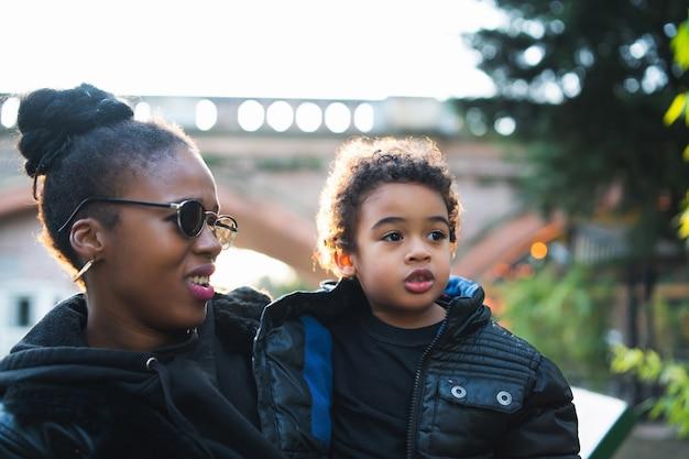 Retrato de una madre afroamericana con su hijo de pie al aire libre en el parque, divirtiéndose. familia monoparental.