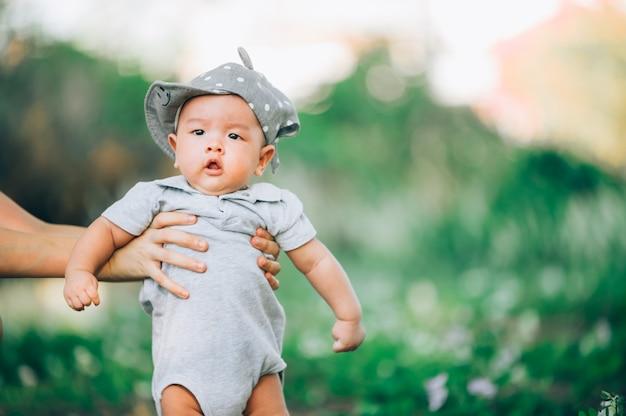 Retrato de una madre asiática que sonríe con su bebé de 3 meses en la hierba verde al aire libre en parque.