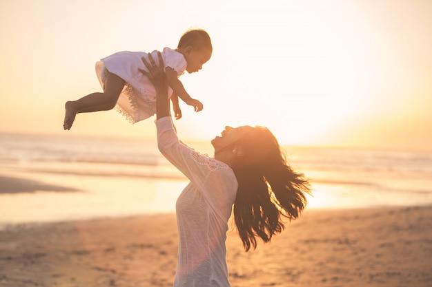 Retrato de madre y bebé en la playa al atardecer