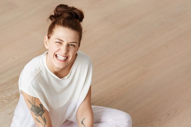 Retrato de madre divertida juguetona sentada en el suelo en posición de loto en ropa blanca. joven mujer caucásica con un denso montón de cabello castaño haciendo muecas, haciendo muecas, mostrando los dientes de manera enojada.