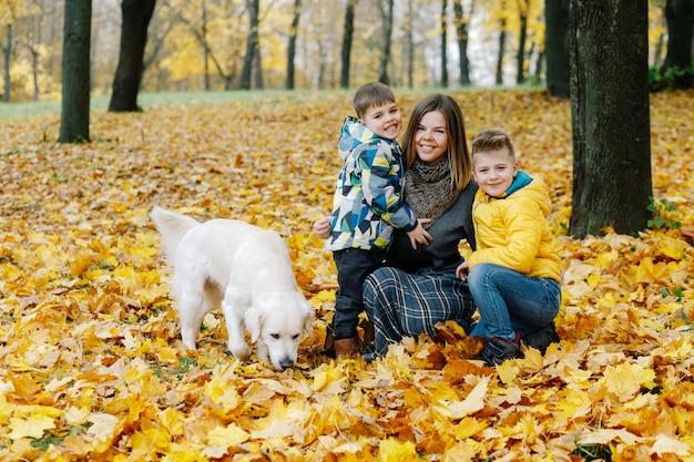 Retrato de una madre con dos hijos y un perro en un parque de otoño