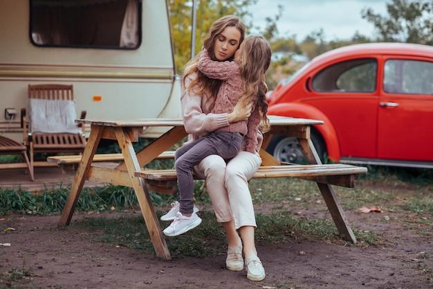 Retrato de madre e hija abrazándose y relajándose en el campo en autocaravana vacaciones con coche retro rojo