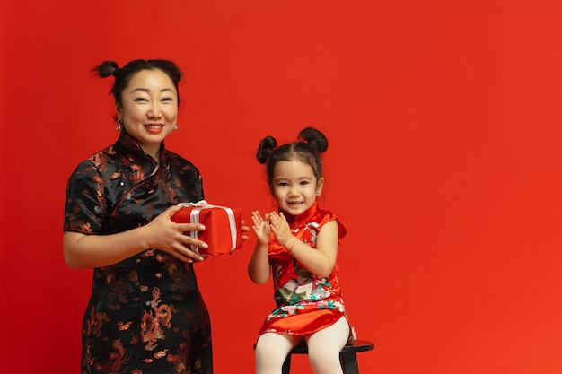 Retrato de madre e hija asiática aislado en la pared roja en vestimentas tradicionales