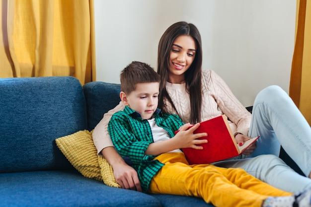 Retrato de madre e hijo leyendo un libro en casa