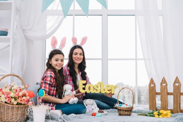 Retrato de la madre y la hija sentada cerca de la ventana con la palabra de pascua y el conejito en la mano