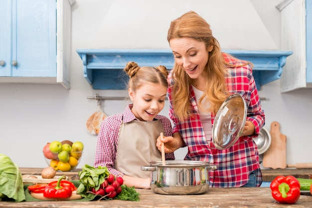 Retrato de una madre y una hija sonrientes mirando comida preparada en mesa de madera