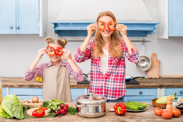 Retrato de una madre y una hija sonrientes que sostienen la rebanada de la pimienta roja delante de los ojos que miran la cámara