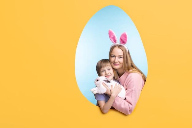 Retrato de madre joven feliz en diadema de orejas de liebre abrazando conejito con hijo, marco en forma de huevo