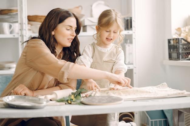 Retrato de madre y niña formando arcilla juntos
