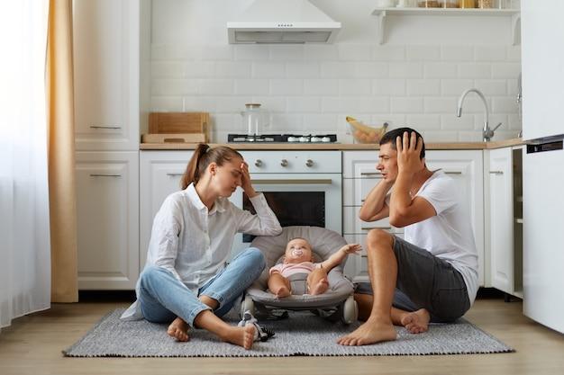 Retrato de madre y padre sentados en el piso de la cocina con el pequeño hijo o hija en una mecedora en el piso de la cocina, los padres cansados y sin dormir manteniendo las manos en la cabeza, necesitan descansar.