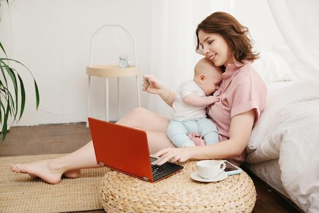 Retrato de la madre y el pequeño hijo haciendo compras en línea con tarjeta de crédito, usando la computadora portátil.