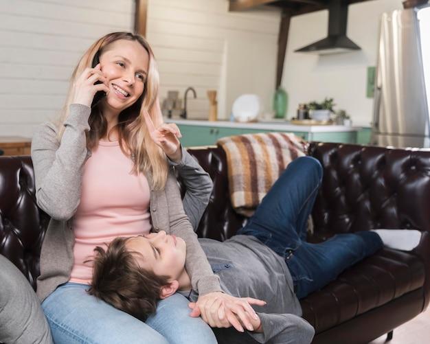 Retrato de madre relajante con hijo en el sofá