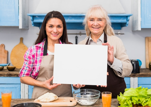 Retrato de la madre senior y su joven hija sosteniendo una tarjeta blanca en blanco de pie en la cocina