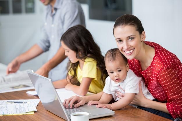 Retrato de la madre sonriente que trabaja en la computadora portátil con el bebé