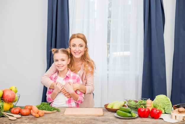 Retrato de una madre sonriente y su hija de pie detrás de la mesa de madera mirando a la cámara