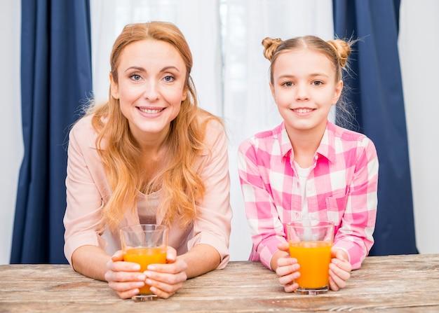 Retrato de una madre sonriente y su hija sosteniendo un vaso de jugo mirando a la cámara