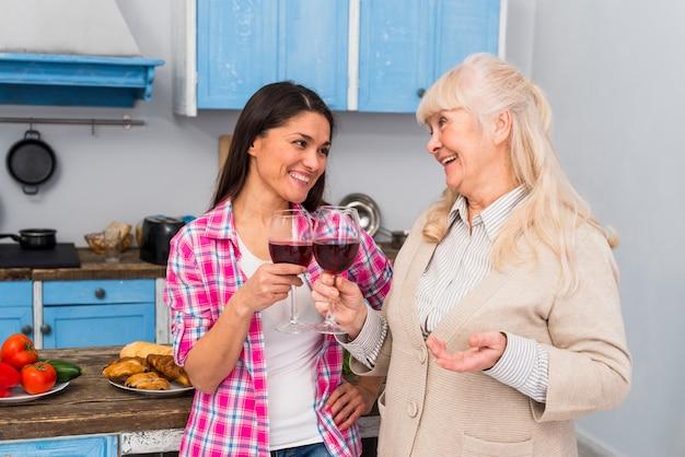 Retrato de madre sonriente y su joven hija tostando vinos tintos