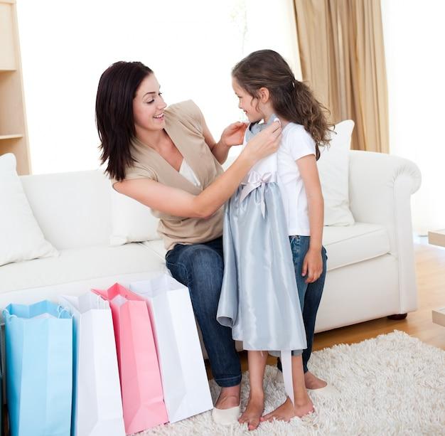 Retrato de una madre y su hija probándose un vestido