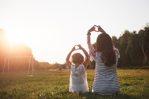 El retrato de una madre y su niña conforman su corazón en el parque.