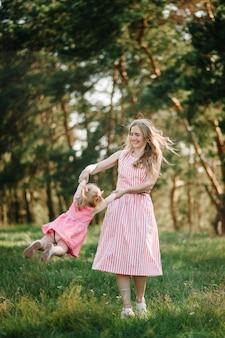 Retrato de una madre vomita y hace girar a la hija en manos de la naturaleza en las vacaciones de verano. mamá y niña jugando en el parque a la hora del atardecer. concepto de familia amistosa. de cerca.