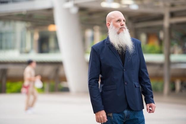 Retrato de maduro empresario calvo con barba larga en las calles de la ciudad al aire libre