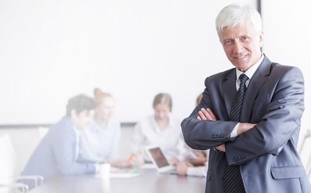 Retrato, de, maduro, hombre de negocios, delante de, su, equipo, en, oficina