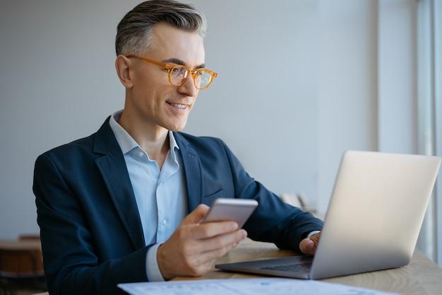 Retrato, de, maduro, hombre de negocios, utilizar, computadora portátil, mecanografiar