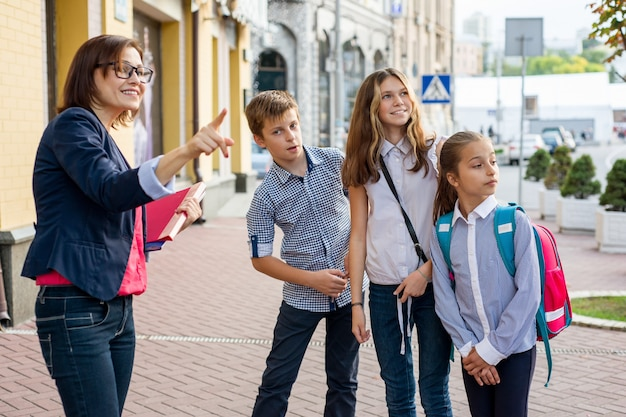 Retrato de maestra con niños de pie fuera de la escuela