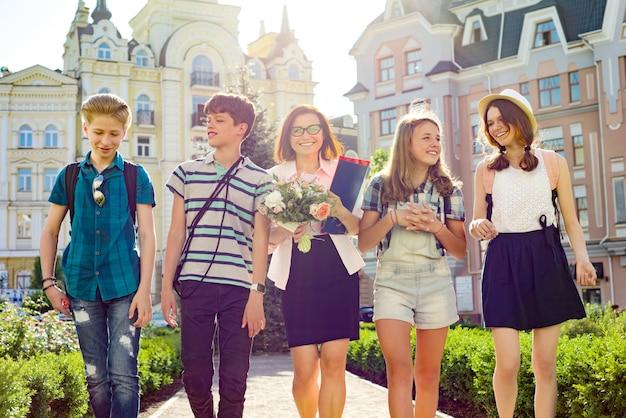 Retrato de maestra de secundaria con ramo de flores y estudiantes del grupo