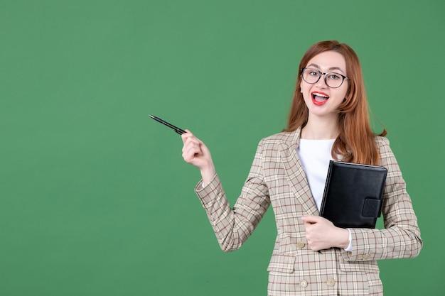 Retrato de maestra sosteniendo el bloc de notas en verde