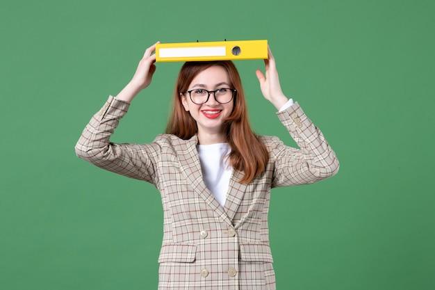 Retrato de maestra sosteniendo documento amarillo sobre su cabeza verde