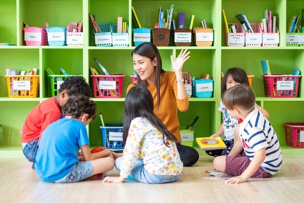 Retrato de un maestro asiático enseñando a niños en una escuela internacional