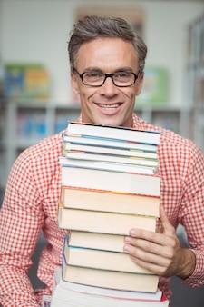 Retrato de maestro de escuela sosteniendo la pila de libros en la biblioteca