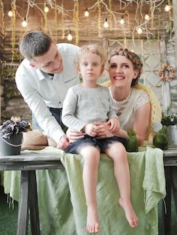 Retrato de mamá, papá e hija en la acogedora sala de estar