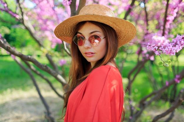 Retrato de manantial de linda mujer sonriente en elegante vestido coral, con sombrero de paja disfrutando de día soleado