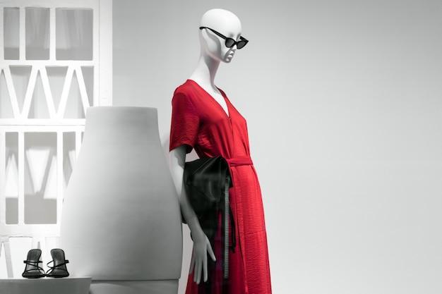 Retrato de maniquí femenino en gafas de sol y vestido rojo. venta y tema publicitario. copyspace para texto