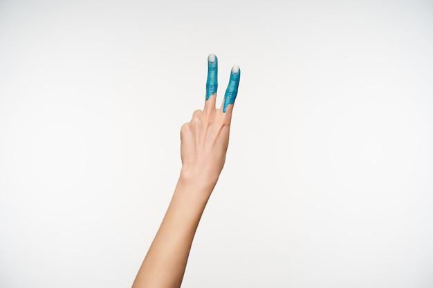 Retrato de la mano femenina levantada mostrando dos dedos pintados en color azul mientras forma un gesto de victoria, estando aislado en blanco