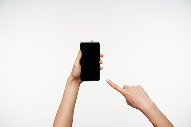 Retrato de manos de mujer joven levantadas mientras mantiene el teléfono inteligente en él y se muestra en la pantalla con el dedo índice, aislado en blanco