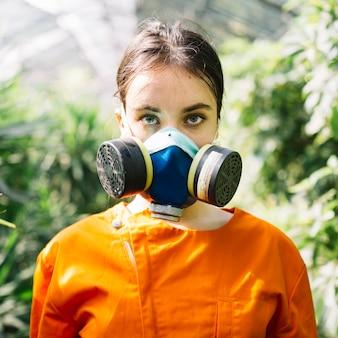 Retrato de una máscara de contaminación vistiendo de jardinero mujer