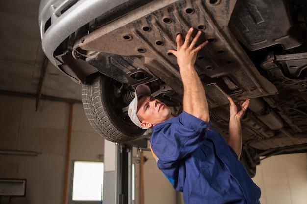 Retrato de mecánico de automóviles trabajando con herramientas debajo del automóvil