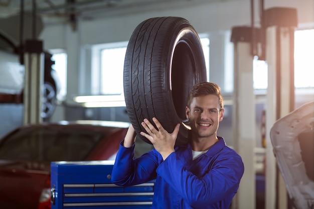 Retrato del mecánico que lleva un neumático