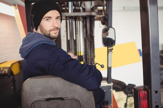 Retrato de mecánico sentado en carretilla elevadora