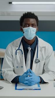 Retrato de médico afroamericano mirando a la cámara